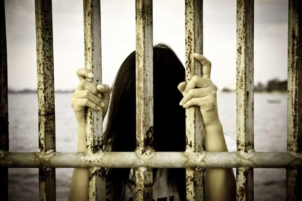 Custodial Justice Hands of the prisoner on the prison